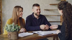 Loving couple is purchasing house signing sales agreement with housing agent, getting key and hugging after making deal. Loving young couple is purchasing house stock video footage