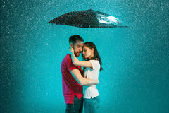 The loving couple in the rain. With umbrella on a turquoise background Stock Photography