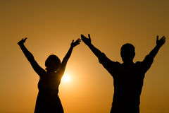Loving couple raise their hands with enjoy at sunset. Silhouette of loving couple raise their hands with enjoy over orange sunset background Stock Photo