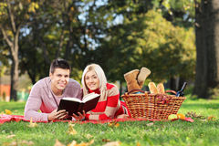 A loving couple reading a book in a park Stock Photos