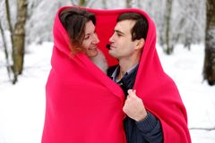 Loving couple with a red blanket in the winter Royalty Free Stock Image