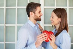 A loving couple with a red heart laugh. Stock Photo