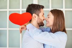 A loving couple with a red heart laugh. Stock Images
