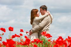 Loving couple on red poppies field Royalty Free Stock Photos