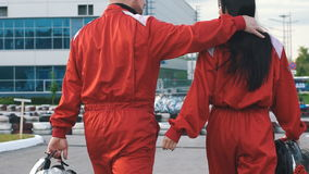 Loving couple in red racing suits go to the race stock video