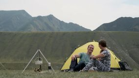 Loving couple relax in nature in front of the tent. Man and girl are working and kissing. Loving couple of tourists relax in nature in front of a tent and a stock video footage