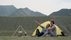 Loving couple relax in nature in front of the tent in sunny weather. stock footage