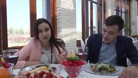 Loving couple at restaurant is having supper, the guy is feeding the girl a salad slow motion stock footage video. Loving couple at the restaurant is having stock video