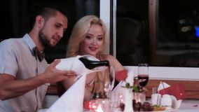 Loving couple in the restaurant, Valentine`s Day, romantic date, the evening for lovers, boys and girls in a romantic. Atmosphere in the cafe, beautiful table stock video footage