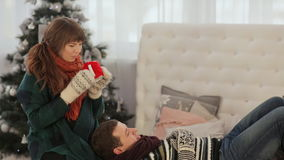 A loving couple is resting on the bed and drinking hot tea. Warm Christmas Eve. stock video footage