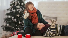 A loving couple is resting on the bed and showing the viewer the thumbs up. Good mood. Warm Christmas Eve. stock footage