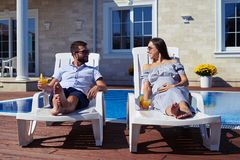 Loving couple resting on lounge chairs in front of house with po Stock Images