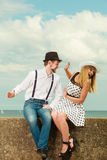 Loving couple retro style dating on sea coast. Summer holidays love relationship and dating concept - romantic playful couple retro style flirting on sea shore Stock Image