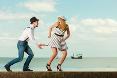 Loving couple retro style dating on sea coast. Summer holidays love relationship and dating concept - romantic playful couple retro style flirting on sea shore Stock Images