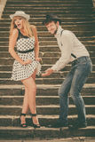 Loving couple retro style flirting on stairs Stock Images