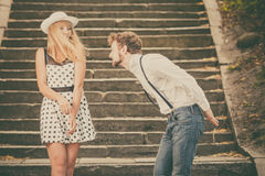 Loving couple retro style flirting on stairs. Summer holidays love relationship and dating concept - romantic playful couple retro style flirting on city stairs Stock Images