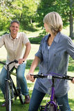 Loving couple riding bicycles in park Stock Photos