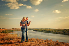 Loving couple on the river bank. Royalty Free Stock Photography