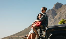 Loving couple on a roadtrip. Man sitting on car hood and hugging his girlfriend. Loving couple on a roadtrip stock photo