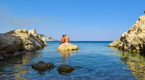 The loving couple on the rock. The loving couple on the rock in sea. Marathias beach, Zakynthos Island, Greece royalty free stock photo