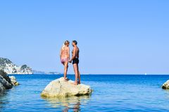 The loving couple on the rock. The loving couple on the rock in sea. Marathias beach, Zakynthos Island, Greece royalty free stock photography