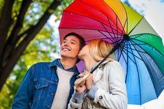 Loving couple on romantic date under autumn umbrella. Royalty Free Stock Photos