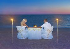 Loving couple at romantic dinner with torch flares, candles and Royalty Free Stock Photography