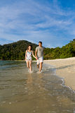 Loving couple running along the beach Royalty Free Stock Photography