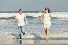 Loving couple running on the beach at the day time. Stock Photo