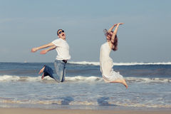 Loving couple running on the beach at the day time. Stock Image