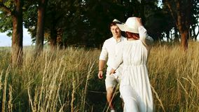 Loving Couple Running in Countryside Park. Carefree loving newlyweds running in countryside park, having fun together, trusting relations stock video footage