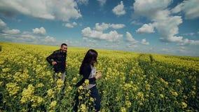 Loving couple runs across the field stock video