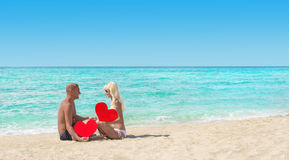 Loving couple at sandy sea beach with red hearts - St. Valentine Stock Photos