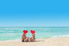 Loving couple at sandy sea beach with red hearts - St. Valentine Stock Photo