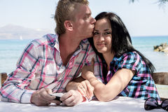 Loving couple on sea background. Couple in love on the background of the sea, a men blonde and brunette girl Royalty Free Stock Image