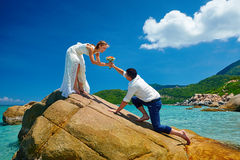 Loving couple on sea beach - a man making proposal with bouquet royalty free stock images