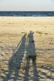 Loving couple shadows. Long shadow of young couple holding hands cast on beach sand stock image
