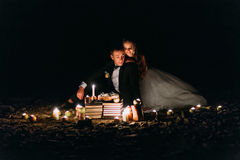 Loving couple share a romantic dinner with candles and cake  at beach, coast against wonderful night Stock Photos