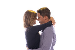 Loving couple share a tender moment. Hugging and looking into each others eyes with beautiful smiles of love, isolated on white Stock Images