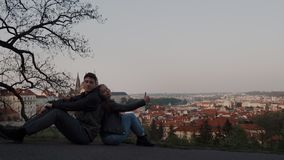 Loving couple sit back to back on observation deck with panoramic view of Prague, they joyfully look at camera and show. Likes 4k stock video footage