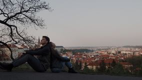 Loving couple sit back to back on observation deck with panoramic views of Prague and they are dreaming. 4k stock footage