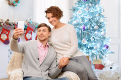 Loving couple sitting in the arm chair Stock Images