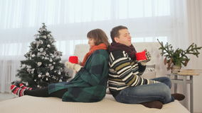 A loving couple is sitting back to back and drinking hot coffee. Christmas Eve. Warm New Year`s atmosphere. stock video footage
