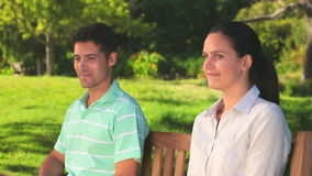 Loving couple sitting on a bench. Adorable couple sitting and smiling on a bench in a park stock video footage