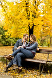 Loving couple sitting on the bench in the autumn park. Young loving couple sitting on the bench in the autumn park Stock Photos