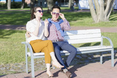The loving couple is sitting on the bench. Stock Image