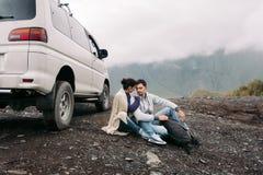 Loving couple sitting on a blanket near a car on a hillside stock photo