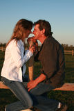 Loving Couple. Sitting on a country fence in the sunset Royalty Free Stock Photography