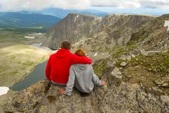 A loving couple sitting on the edge of a rock embraces in front royalty free stock image