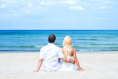 Loving couple sitting and embracing on the beach. Loving couple sitting and embracing on a tropical summer beach Royalty Free Stock Photo